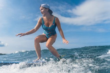 side view of woman in cap and swimming suit surfing in ocean