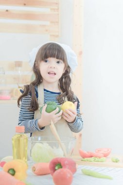 Cute girl prepare healthy food salad in kitchen room.