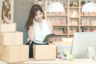 Young entrepreneur checking products stock on the smart tablet while talking to her customer at home office