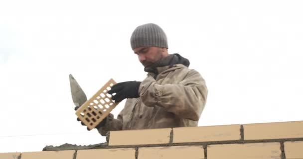 Handyman na vysokostaveništi provádí svou práci pokládání cihel zdivo fasády budovy, zedník vytváří cihlovou zeď nové budovy ve výšce, vysoce kvalitní cihly pokládání, stavitel v práci