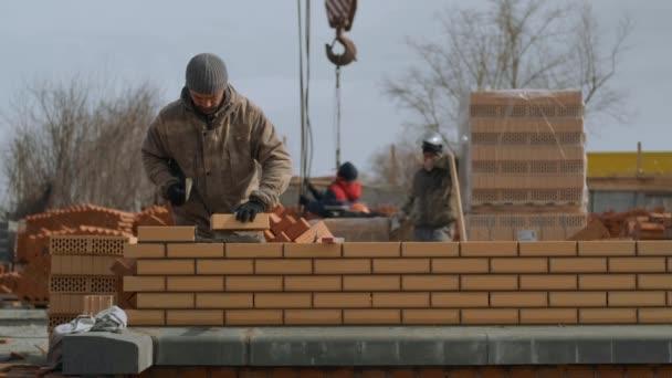 Mason pracovník staví cihly, Mladý usmívající se zedník staví cihlové budovy, Stavitel zvedá cihly slámy barvy a vrstvy v linii, Pracovník pomocí cementu vytváří cihlovou zeď, Worclays je přímé vedení