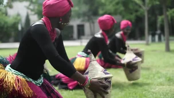 Tři ženy v Africe tanec lidový tanec v tradičních kostýmech s košíky