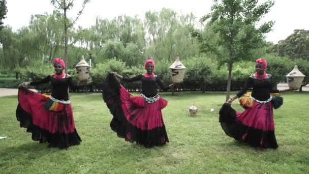 Three african women dancing a folk dance in traditional costumes with baskets