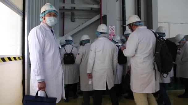Exkurze do továrny, lidé v bílých hábitech procházejí továrna workshop, který dělá transformátory