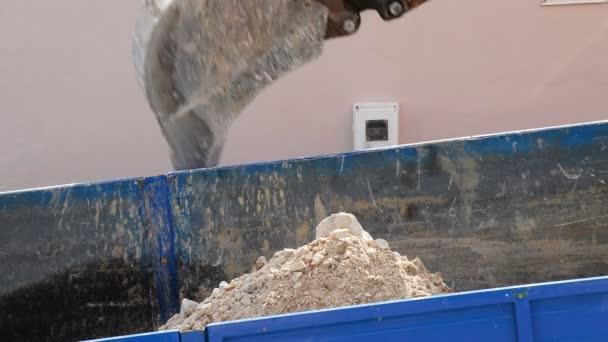 Rypadlo čepel uložení písku v náklaďáku. Stavebnictví