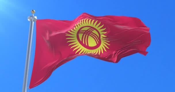 Flag of Kyrgyzstan waving at wind with blue sky in slow, loop