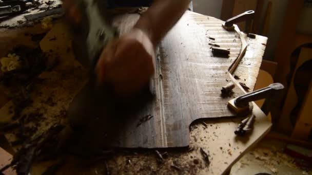 Gitarrenbauer, die Arbeiten an der Spitze einer Gitarre mit einem Holz Hobel in einem workshop