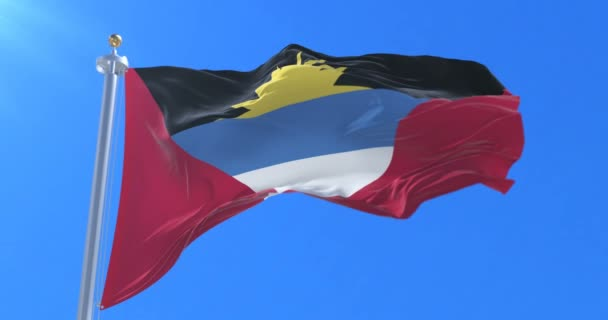 Antigua and Barbuda flag waving at wind in slow with blue sky, loop