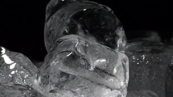 Kostky ledu tání, otáčení na černém pozadí