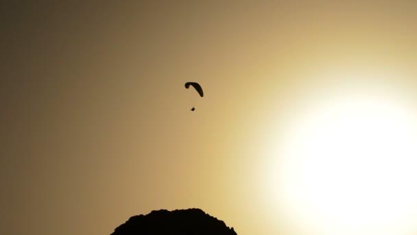 Kluzák praktikování sport paragliding při západu slunce, podsvícení