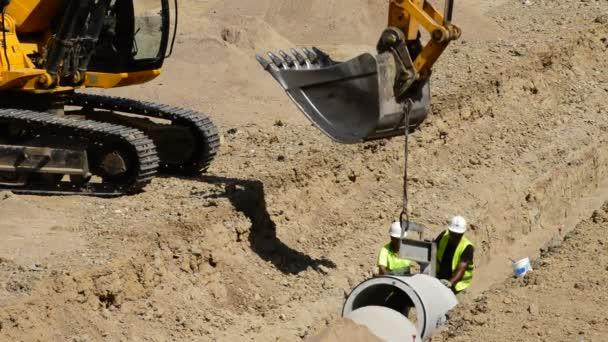 Zaměstnanci s bagrem, pokládání potrubí v příkopu