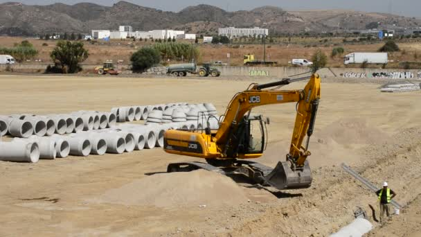 Excavator digging trench with large pipes