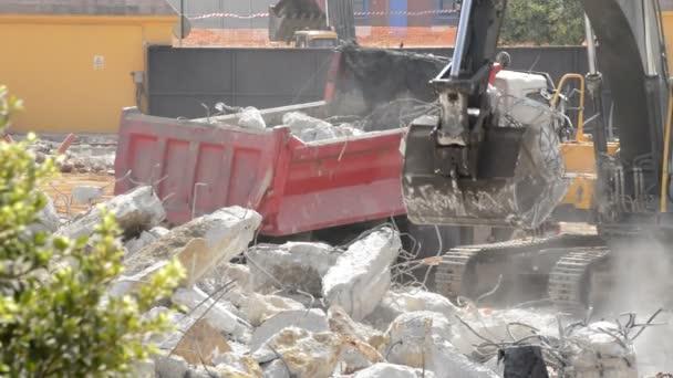 Excavator loading debris in a construction truck during a building demolition