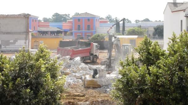 Rypadlo načítání trosky do kamionu během demolice a slunečný den