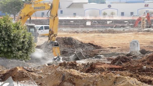 Hammer excavator hitting debris in a demolition of a building
