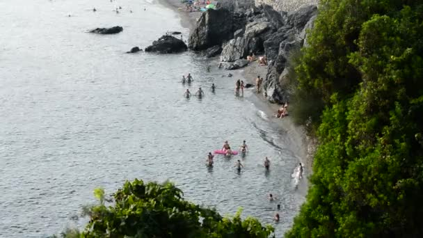 Small mediterranean beach with bathers on a summer day