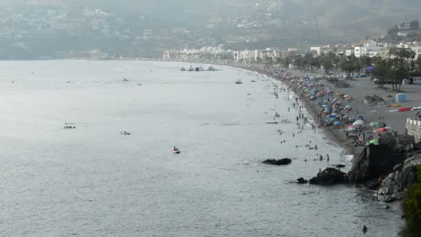 Landscape of mediterranean beach with crowd of people bathing in summer at sunset