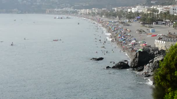 Landscape of mediterranean beach with crowd of people bathing in summer