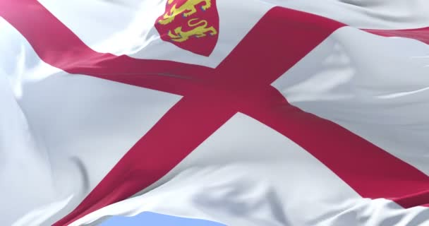 Flag of Jersey waving at wind with blue sky, loop