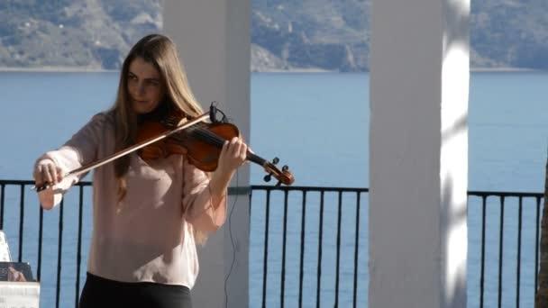 Nő utcai zenész játszik hegedű, egy napsütéses napon a sétányon, Nerja, Spanyolország