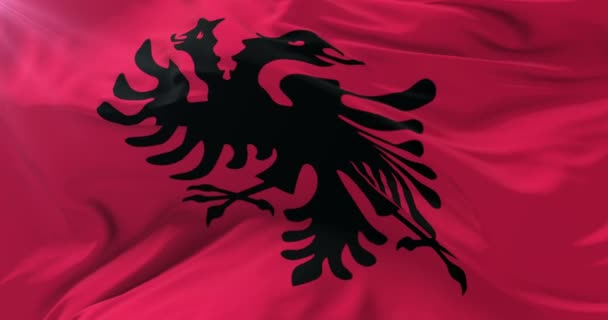 Albanian flag waving at wind with blue sky, loop