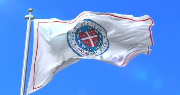 Oklahoma city flag, city of USA or United States of America, waving at wind in blue sky, slow - loop