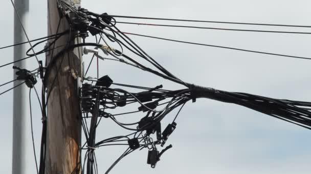 Kabely drát různých služeb, špatně nainstalované na dřevěný sloup