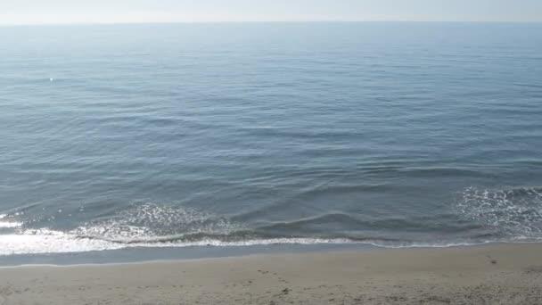Modré moře vlny přijíždějící na pláž slunečný den