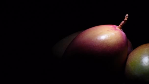 Mangoes gyrating in black background with intimate light