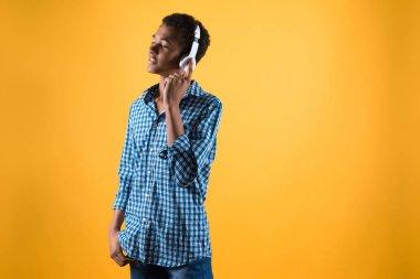 African American teenager in headphones listens to music.