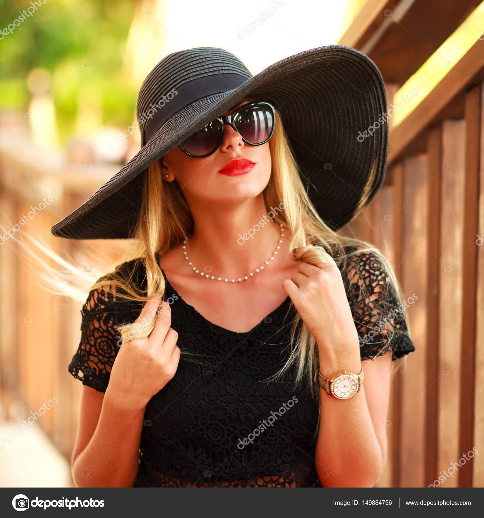 c04b078bb84c0 Glamour jeune femme au grand chapeau noir en parc d'été– images de stock  libres de droits