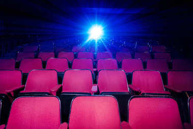 Movie theater with empty seats and projector
