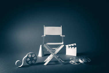 High contrast vintage image of Director chair and several movie items made from paper on a wood surface stock vector