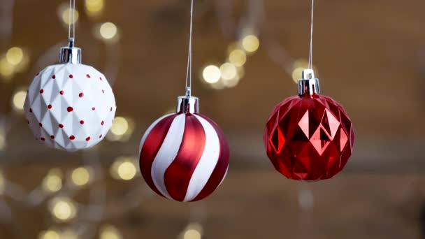 Christmas decorations, three balls hanging on the bokeh background of lights.
