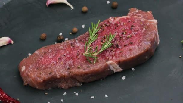 Hovězí svíčková syrové steaky s kořením na tmavém stole.