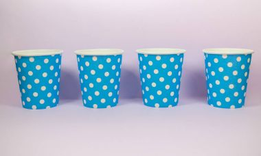Blue polka dot paper cup on the pink background