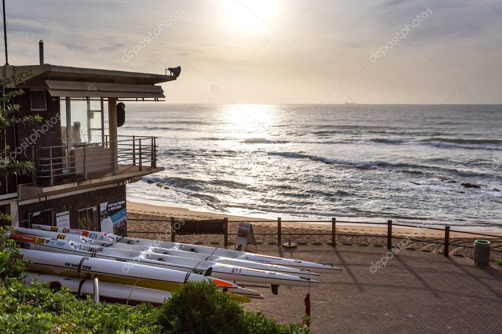 Durban, South Africa, April 9 - 2018:  View out to sea with Lifeguard building in left corner and sea canoes at dawn.