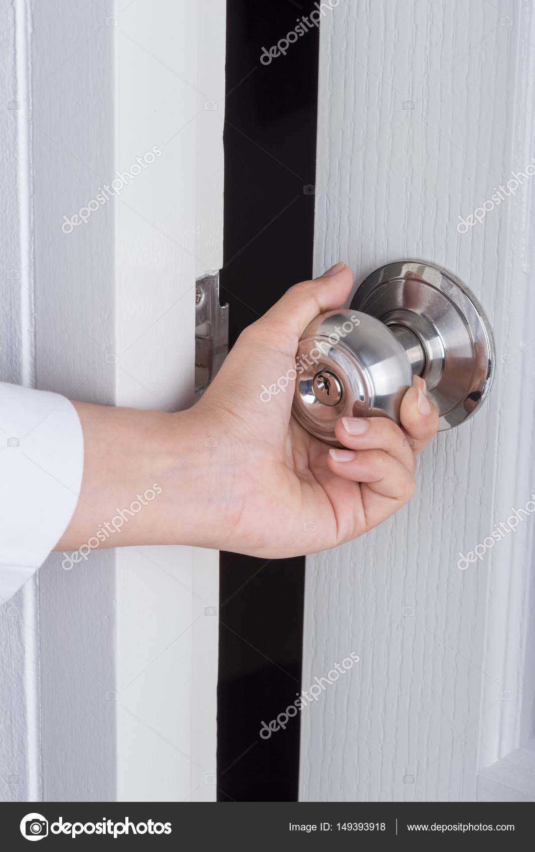 Hand opening door knob on white door — Stock Photo © geargodz #149393918