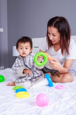 baby playing toys with mother on bed