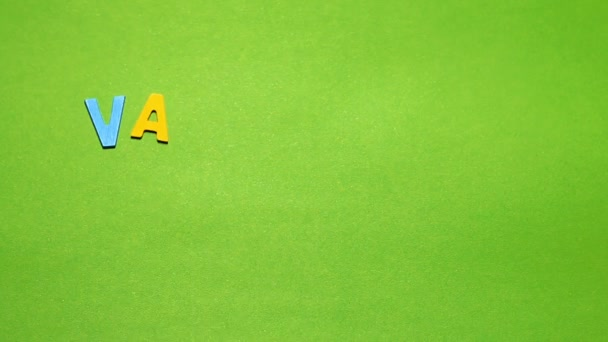 Wood characters of different colors arranged in a word Valentines day on a green background with blur effect