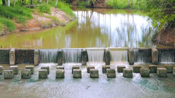 Folyamatos víz mozgását jelenet a gát és a gát, hogy lassítják az áramlást, a víz a folyóba. Vannak friss zöld területek Thaiföldön.