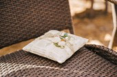 close-up photo of beautiful wedding decoration of little pillow outdoor on chair background