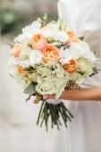 Detailní foto krásná nevěsta v bílých šatech pózuje s svatební kytice