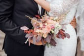 close-up photo of young stylish couple holding flowers bouquet at wedding day