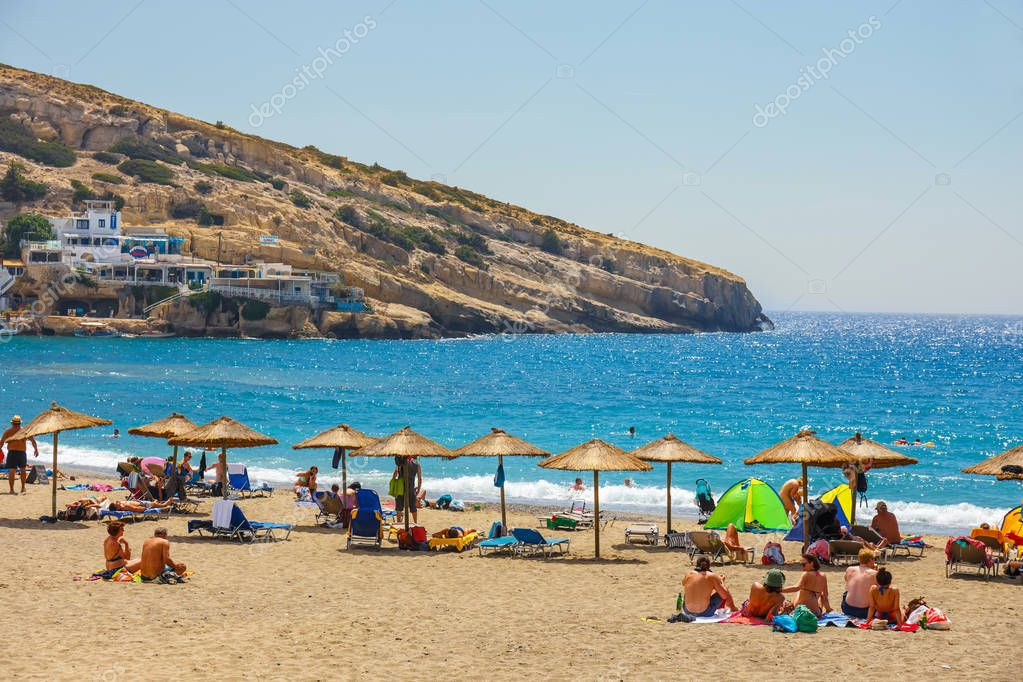 Crete Island, Greece, June 09, 2017: Panorama of Matala beach. Caves on the rocks were used as a roman cemetery and at the decade of 70's were living hippies from all over the world, Crete, Greece