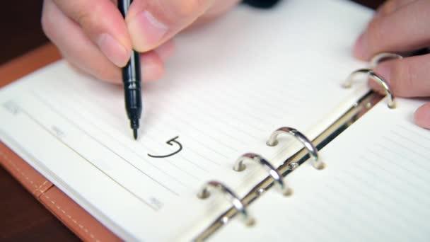 Közelkép egy üzletember kézírási céljairól és listájáról a naplóban.