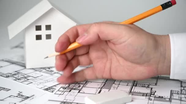 A man who holds a pencil in his hand and paints architectural drawings.