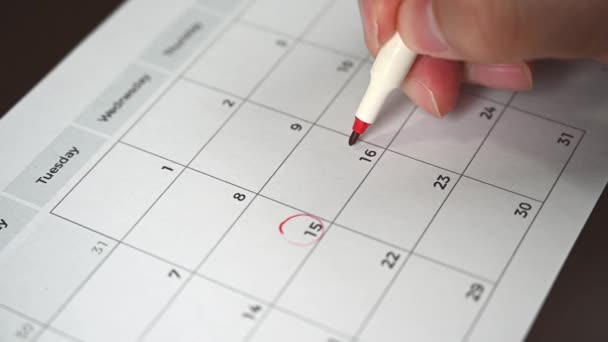 slow motion. The hand of a man holding a pen in his hand and recording his schedule on a desk calendar.