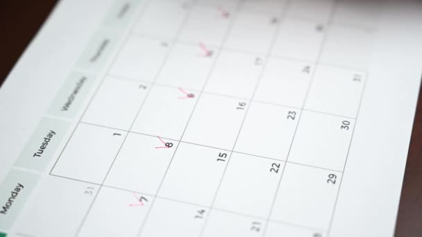 The hand of a man holding a pen in his hand and recording his schedule on a desk calendar