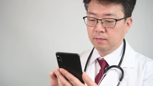 4K. Middle-aged Asian male doctor who uses a smartphone to take telemedicine.